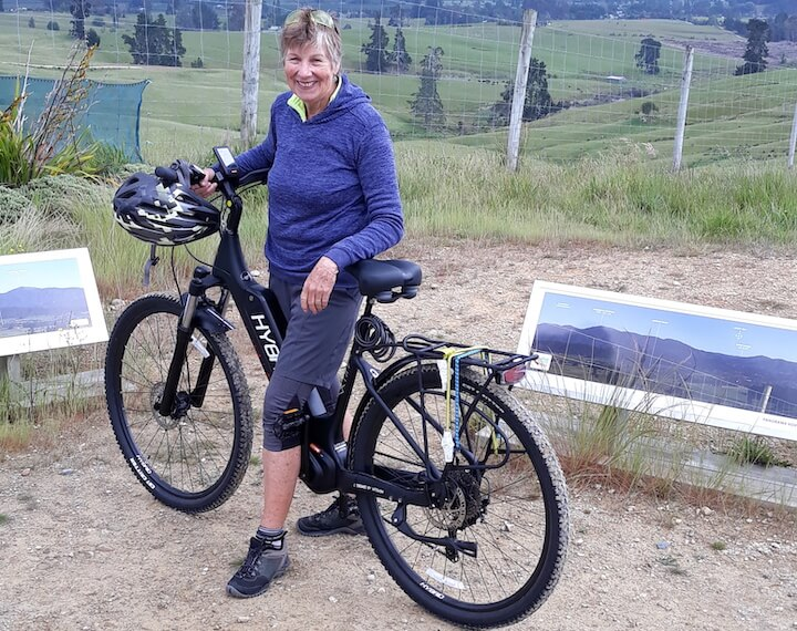 Woman with Hybrid E-Bike on top of hill